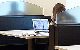 Student seated in a booth working, on a laptop
